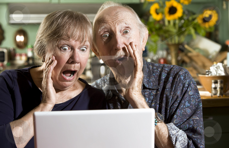 Shocked Senior Couple with a Laptop Computer stock photo, Shocked Senior Couple in their Dining Room with a Laptop Computer by Scott Griessel