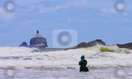 Extreme Fishing stock photo, A lone fisherman braves the rising tides and crashing waves of the ORegon Coast as the Tillamook Rock Lighthouse looms in the distance by Mike Dawson