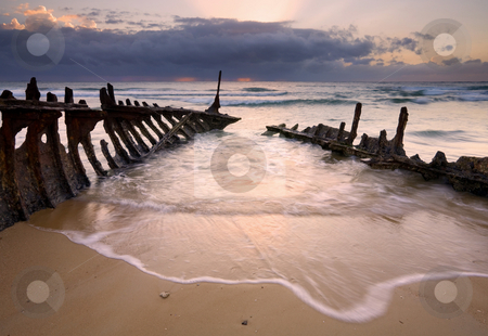 Taking on Water stock photo, The rusting skeleton of the S.S. Dicky Ran Aground in 1893 and still its remains are found on the beach near Caloundra. The incoming tide would rush inside the hull as it were only to recede as the light of sunrise illuminated the water and wet sand. by Mike Dawson