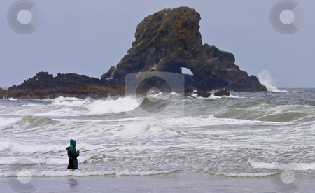 A different kind of Fishing hole stock photo, A brave and resolaute lady fishes in front of stone arch along the Oregon coast. Definitely not your typical fishing hole. by Mike Dawson