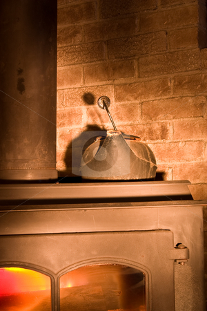 Fire Place With a Kettle stock photo, Water Kettle on a warm fireplace in a corner by Johan Knelsen