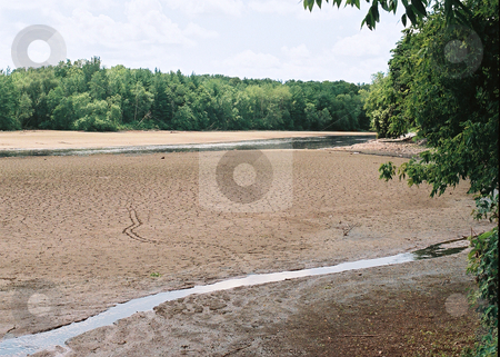 Dry river bed in Wisconsin stock photo, Cracked clay and soft mud imply the affects of dry weather on the Rock River bed in Wisconsin. by Bruce Peterson