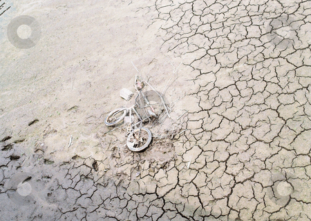 Modern artifact_ bicycle on dry river bed stock photo, The draining of the Rock River left this bike embedded as a sureal fossil in the cracked clay. by Bruce Peterson