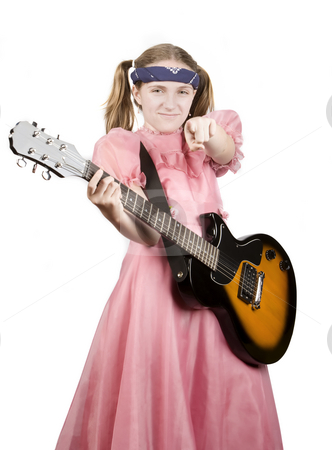 Young Girl with a Rock Guitar Pointing to the Audience stock photo, Young girl in a pink dress with an electric rock guitar pointing by Scott Griessel