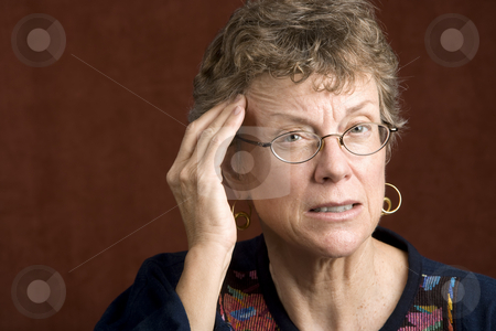 Woman with a headache stock photo, Senior woman with a headache rubbing her temple by Scott Griessel