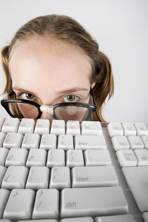 Young Nerdy Girl with a Keyboard stock photo, Nerdy Young Girl Peeking Over a Computer Keyboard by Scott Griessel