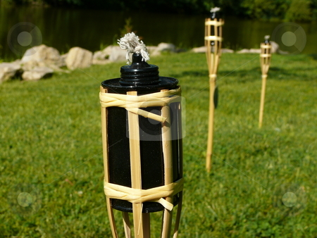 Mini tiki torches stock photo, Mini tiki torch in foreground at close up, with other tiki torches in the backround in soft focus, with beautiful green grass, and a lake in the deeper backround. by Deb Mohling