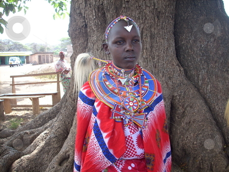 Young Masai girl under a tree stock photo, A beautiful young Masai girl dressed in traditional/cultural clothes and beads by Rose Nthiwa