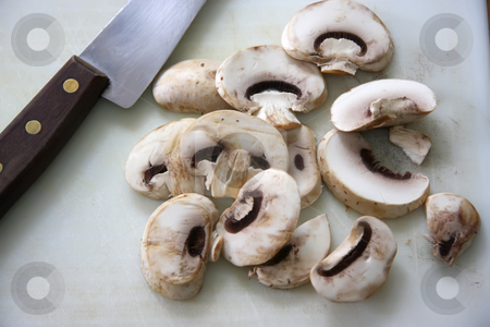 Sliced mushrooms stock photo, Sliced button mushrooms on chopping board with knife by Kheng Guan Toh