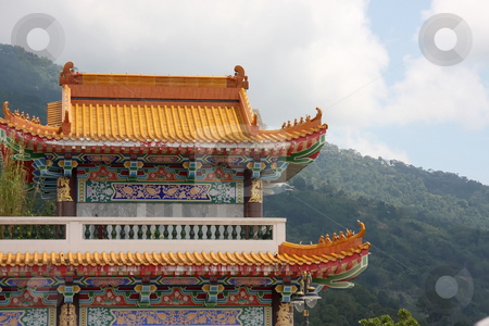 Traditional chinese temple stock photo, Architectural detail of  traditional chinese temple  rooftop against mountains by Kheng Guan Toh