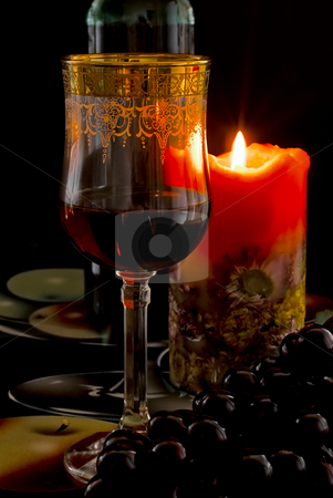 Goblet wine stock photo, Goblet red blame, candle, on back plan bottle blame by Vadim Maier