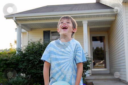 Laughing boy playing in his front yard stock photo, Six year old boy laughing and playing in his front yard. by Heather Shelley