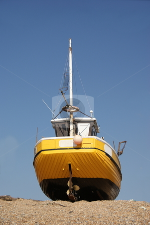 Yellow Boat stock photo, Yellow boat on a beach out of the sea by David Nebesky