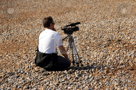 Cameraman on a beach stock photo, Cameraman shooting from a distance on a beach by David Nebesky