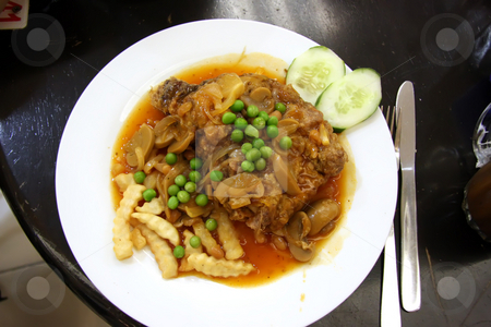 Chicken chop stock photo, Fried chicken chop in gravy with fries and peas by Kheng Guan Toh