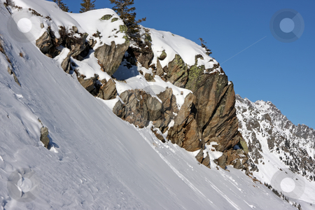 Boulders on snowy mountain stock photo, Snow covered boulders on mountain slope alps in background by Kheng Guan Toh