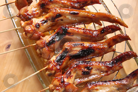 Grilled chicken wings stock photo, Grilled cooked chicken wings on wooden skewers by Kheng Guan Toh