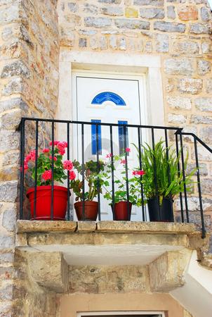 Old stone house in Montenegro - Entrance door stock photo, Entrance door of old stone house with flowerpots in Budva by Julija Sapic