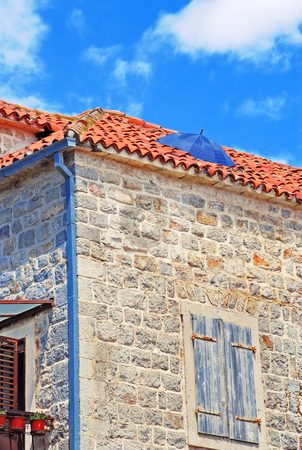 Umbrella on roof. Rain protection stock photo, Old stone house exterior in Montenegro - Budva, umbrella on roof by Julija Sapic