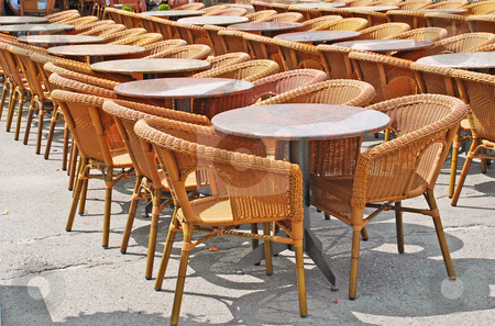 Chairs and tables in row stock photo, Restaurant street terrace with wicker chairs and round tables by Julija Sapic