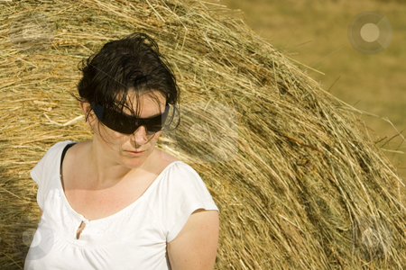 Young woman sitting on hay bail stock photo, Young woman by Ivan Montero
