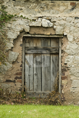 Old delapidated door way stock photo, Old delapidated farm doorway. Weatered wooden door set in a crumbling wall by Chris Pole