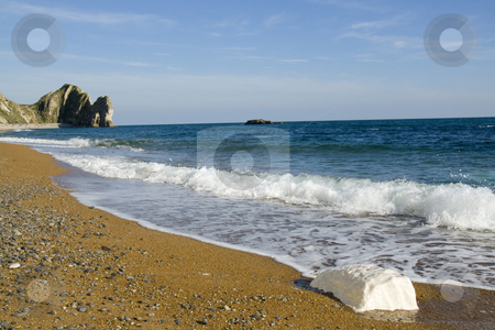 View down beach towards Durdle Door,Dorset England stock photo, Looking along Durdle Door beach towards the Door itself with a wave washed half buried chalk boulder in the foreground by Chris Pole