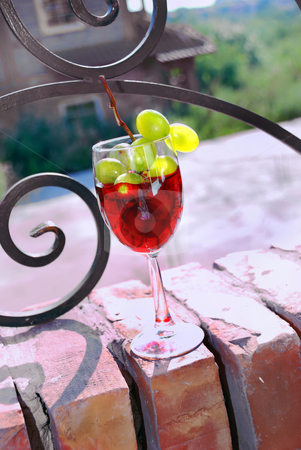 Red wine green grape bunch stock photo, Red wine glass with grape over brick fence by Julija Sapic