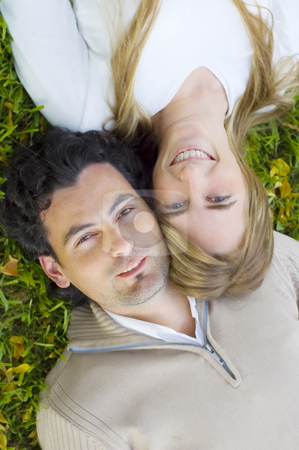 Young Couple Relaxing on a Lawn stock photo, A young couple lying down and relaxing on a grass lawn by Lee Torrens