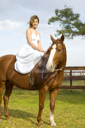 Woman sitting on horse stock photo, A young woman in a white dress sitting side-saddle on a horse by Lee Torrens