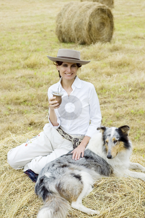 Farm Girl Relaxing stock photo, A young girl relaxes in the field with her dog and a traditional tea by Lee Torrens