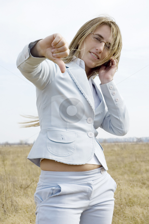 No we didn't get it stock photo, A young businesswoman speaking on a phone on a farm giving the thumbs down. by Lee Torrens