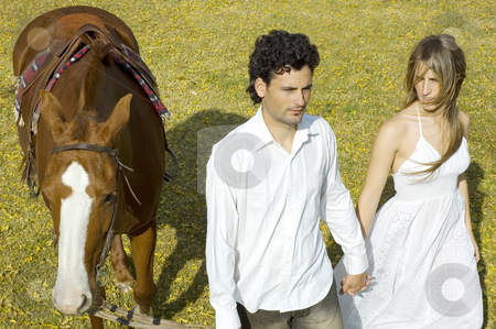 Couple leading horse stock photo, A young couple walking with their horse by Lee Torrens