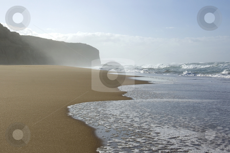 Waves on a deserted beach stock photo, Fresh waves creep up the sandy beach toward the high cliffs. by Lee Torrens