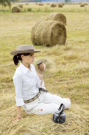 Farm Girl Drinking Mate in a Field stock photo, A young Argentinean farm girl relaxes in the field drinking yerba mate by Lee Torrens
