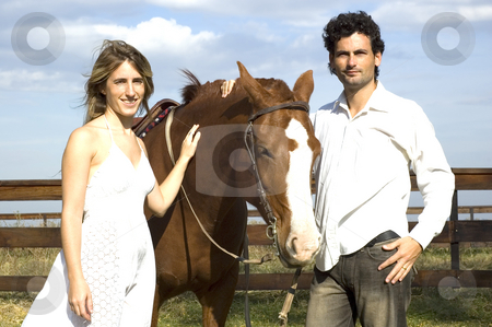 Couple with horse stock photo, A young couple posing with their horse by the fence on a rural farm on a cloudy day by Lee Torrens
