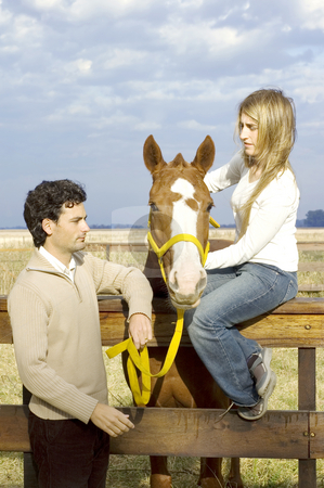 Couple and horse stock photo, A young couple relaxing with their horse by the fence on a rural farm on a cloudy day by Lee Torrens