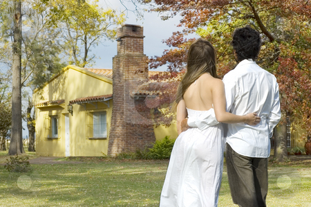 Young Couple looking at a Farm House stock photo, A young couple standing looking at a house on a rural property by Lee Torrens