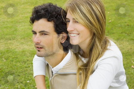 Couple playful stock photo, A young couple playing affectionately in a garden, both looking to the side. by Lee Torrens