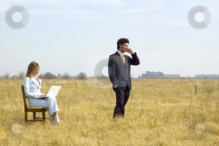Business Team Working Outdoors stock photo, A businessman and businesswoman working in the middle of a dry field. by Lee Torrens