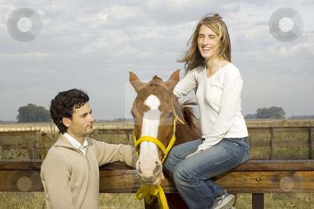 Woman sitting on fence stock photo, A young couple enjoying time with their horse on the farm by Lee Torrens