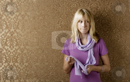 Apprehensive young girl stock photo, Apprehensive young girl leaning against a wall with gold wallpaper by Scott Griessel
