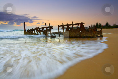 Swallowed by the Tides stock photo, The shipwreck of the S. S. Dicky on a Sunshine Coast Beach in Australia. A 40 ton steamer ran aground in 1893. The sea has gradually carved away at it after over 110 years of the waves washing over it. A glorious sunrise helped illuminate it as the tides began to come in. by Mike Dawson