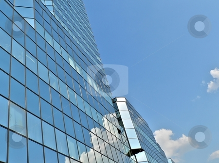 Modern blue skyscraper  stock photo, Modern blue skyscraper  with clouds reflection by Laurent Dambies
