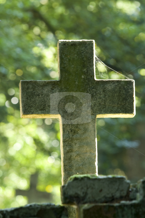 Backlit cross in a graveyard stock photo, Backlit cross in a graveyard with cobweb and a blurred background by Chris Pole