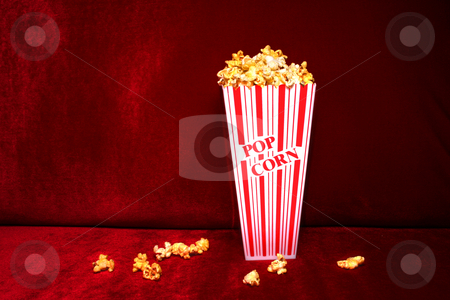 Popcorn stock photo, Theater-style popcorn spilled from tub onto red velvet seat. by Clay Anthony