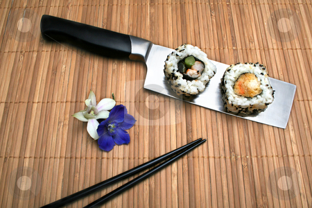 Sushi dinner stock photo, Two pieces of sushi on a Chinese cleaver sitting on a bamboo mat next to flowers and chop sticks. by Clay Anthony