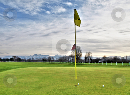 Golf course stock photo, Scenic view of a golf course with mountains in the background by Laurent Dambies
