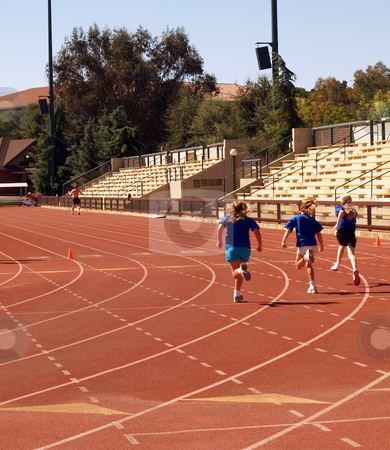 Girls running on track stock photo, Three young girls in shorts and shirts running on track by Jeff Cleveland