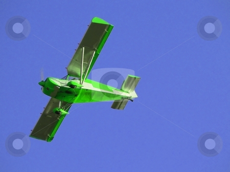 Green  plane stock photo, Small green airplane flying over blue sky by Laurent Dambies
